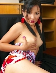 Saiko Kurosawa sits down on a sofa with her tits exposes. She has long black hair that hangs down to her tits.