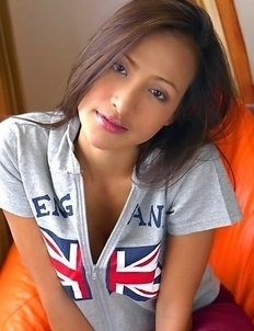 Teaza Tsing sits down on an orange sofa with a zip up England t shirt on.