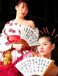 Mona Choi and Mind Sumonrat are dressed up as royalty as they hold their fans in their hands.