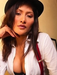 Bella Yong has a hot body and she is not afraid to show it. She is wearing a sexy outfit that consists of a black hat, white top, and suspenders.