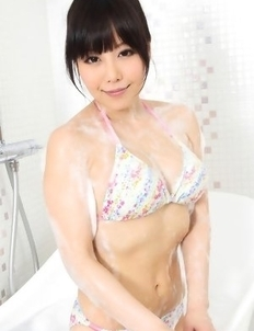 Maria Akamine washes and soaps her body over bath suit