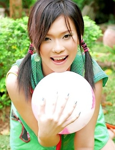 Adorable Ae Marikarn is outside and she is holding gym ball in her hands.