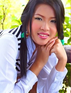 Aime Copony begins posing and she smiles for the camera while wearing a white and black top.