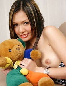 Some things in life you never stop living. That's why cute Far Sarawimol is sitting on the sofa and playing with her favorite teddy bear.